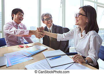 business team shaking hand and laughing happiness for successful working project