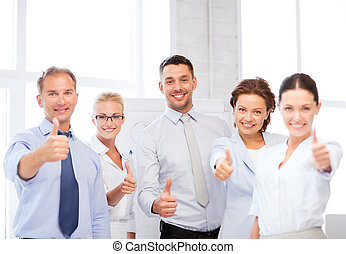 business team showing thumbs up in office - picture of happy...