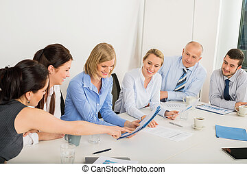 Business Team Sitting Around Meeting Table - Business Team...