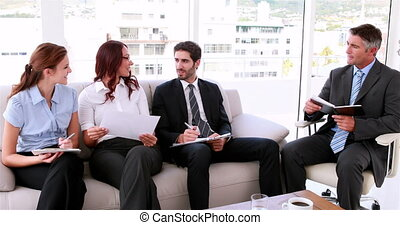 Business team sitting on couch having a meeting in the...