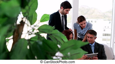 Business team sitting on couch having a meeting using tablet...