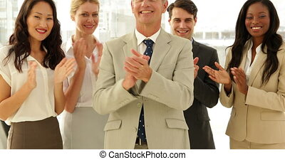 Business team smiling at camera and clapping at the office