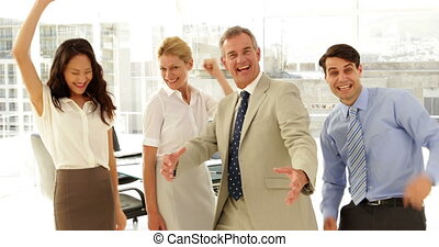 Business team smiling at camera and cheering at the office