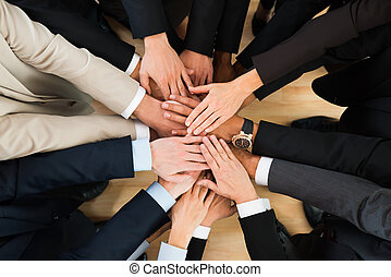 Business Team Stacking Hands On Table - Directly above shot...