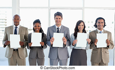 Business team standing upright side by side while showing blank sheets and smiling