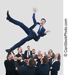 Business team throwing his colleague - Group of jubilant...
