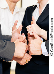Business team thumbs up - Successful business team showing a...