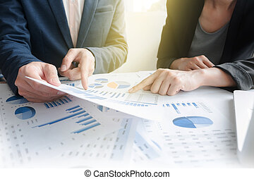Business team two colleagues discussing financial graph data on office table