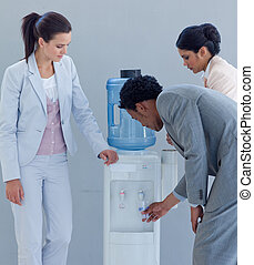 Business team speaking next to a water cooler in office