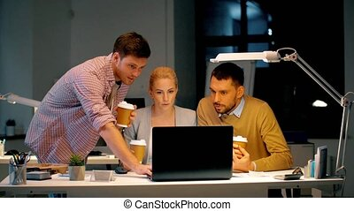 business team with computer working late at office -...