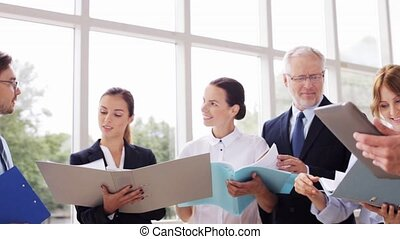 business team with folders and tablet pc at office - people,...