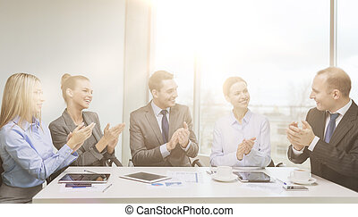 business team with laptop clapping hands