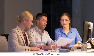 business team with papers working at night office