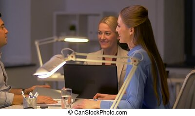 business team with papers working late at office