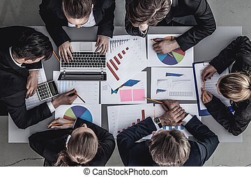 Business team with reports - Top view of business team...