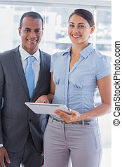 Business team with tablet pc smiling