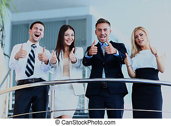 Business team with the thumbs up in a stairs.