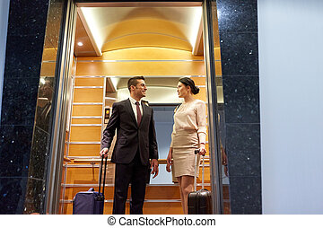 business team with travel bags in hotel elevator