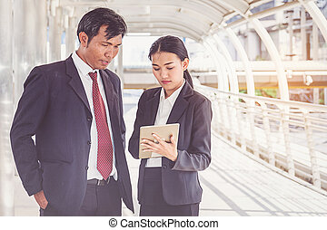 Business team working at city, looking a tablet