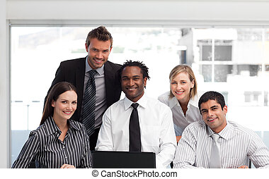 Business team working in an office looking at the camera