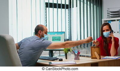 Business team with protection masks respecting social distancing using plexiglass. Freelancers working in in new normal office workplace talking writing on clipboard searching on computer.