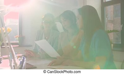 businesswomen discussing papers at office