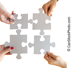 close up of hands connecting puzzle pieces