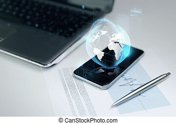 close up of smartphone with earth globe hologram