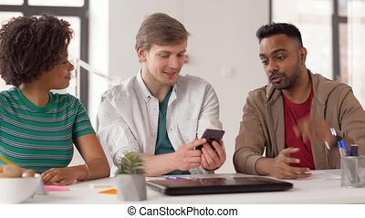 man showing smartphone to coworkers at office - business,...