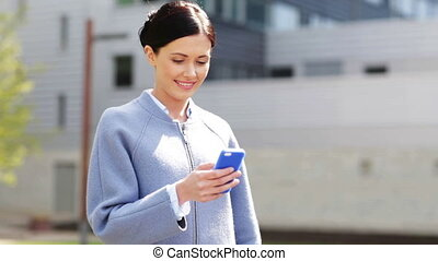 smiling businesswoman with smartphone texting - business,...