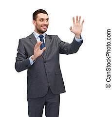 business, technology, communication concept - smiling businessman working with imaginary virtual screen
