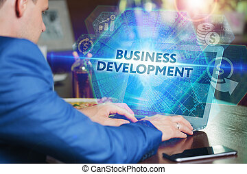 Business, Technology, Internet and networking concept. Young businessman working on his laptop of the future, working with the virtual screen hologram. The inscription on the screen:business development.