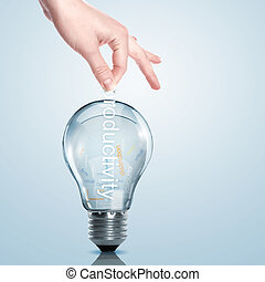 Business term and electric bulb - Hand putting a busines...