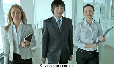 Business three - Smiling business people walking towards the...