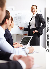 Business training - A businesswoman pointing at whiteboard ...