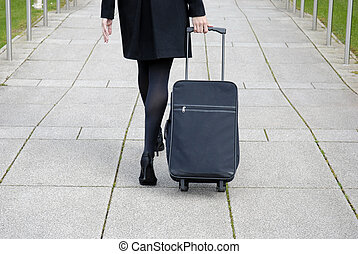 Business Travel - Business woman walking with black...