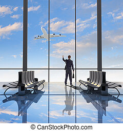 Business travel - Businessman at airport looking at airplane...