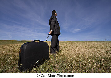 Business travel - businessman with his luggage outdoor in...