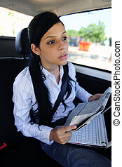 business travel: businesswoman in limousine reading...