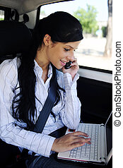 business travel: businesswoman with laptop in car - business...