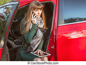 business travel: busy businesswoman with document and laptop in car