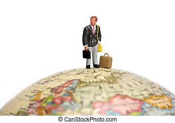 Business travel concept - A miniature businessman stands...