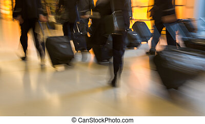 Business travel - Group of businessmen carrying luggage in...