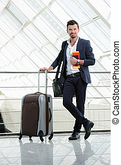Business Travel - Handsome businessman waiting flight...