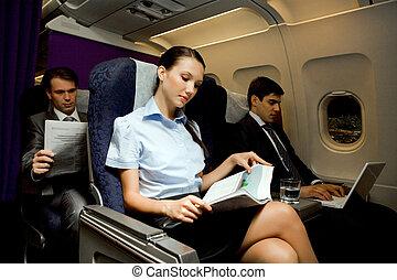 Business travel - Image of pretty girl reading magazine...