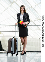 Business Travel - Business woman on plane tickets waiting...