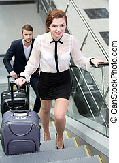 Business Travel - Young business people with a suitcase and...