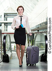 Business Travel - Young business woman with suitcase and...