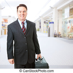 Stock photo of a businessman holding his suitcase and walking through the airport concourse.