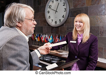 Business traveler - Businessman checking in at the reception...